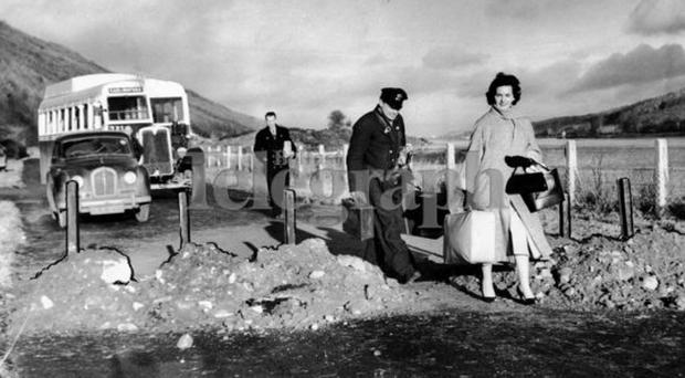 A bus passenger, the bus conductor and driver (from the Carlingford bus) walking across a spiked road. (Some cross-border roads were made impassable to prevent vehicles using them.) 29/1/1958