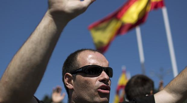 Demonstrators raise their hands as they take part in a protest in Madrid, Spain (AP)