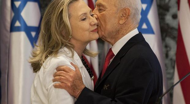 US Secretary of State Hillary Rodham Clinton, left, and Israel's president Shimon Peres, hug after a joint statement in Jerusalem (AP)