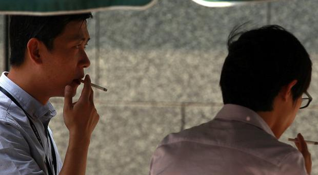 Chinese men smoke in a designated outdoor area in Beijing (AP)
