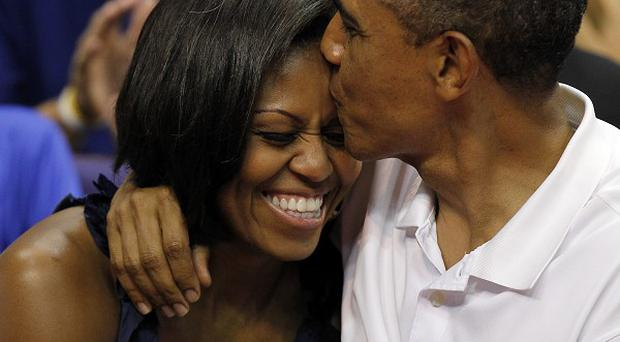 US president Barack Obama kisses the head of first lady Michelle Obama after kissing her for 'Kiss Cam' at a stadium in Washington (AP)