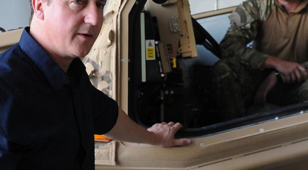 Prime Minister David Cameron is shown a new Foxhound armoured vehicle at Camp Bastion in Afghanistan