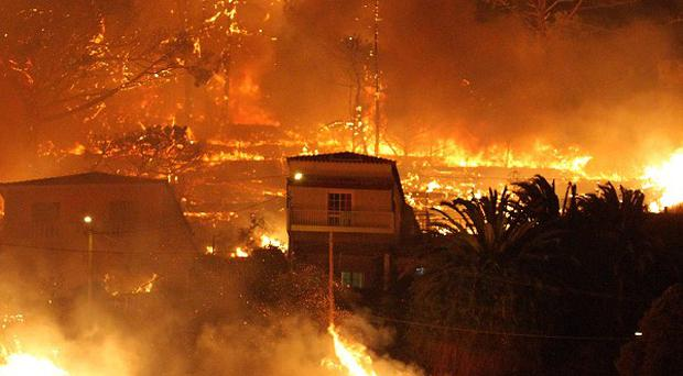 Forest fires rage near houses on the hills above the city of Funchal (AP)
