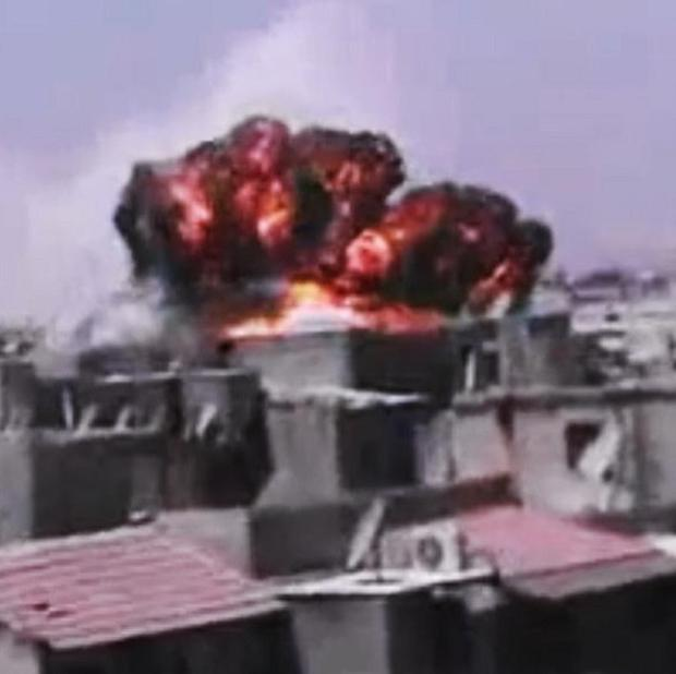 Smoke rises from buildings in Homs, Syria (AP/Shaam News Network via AP video)
