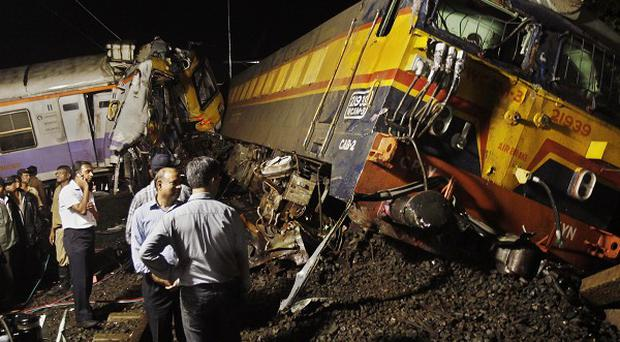 Indian rescue workers work to clear the wreckage of a train collision on the outskirts of Mumbai. (AP)