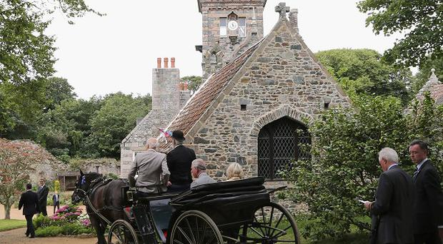The Prince of Wales and Camilla, Duchess of Cornwall, ride in a horse-drawn carriage on the Island of Sark