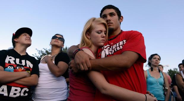 AURORA, CO - JULY 20: Lonnie Delgado (R) hugs Heaven Leek during a prayer for victims at the Century 16 movie theatre where a gunman attacked movie goers during an early morning screening of the new Batman movie,