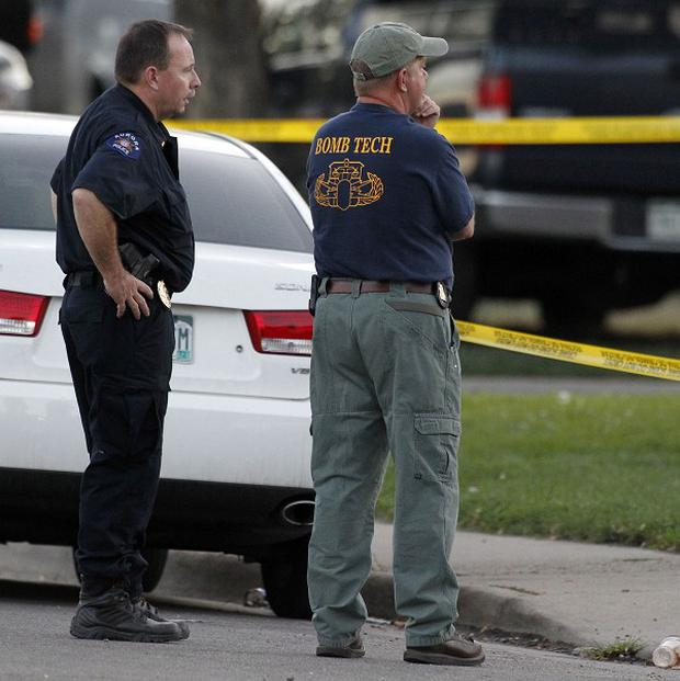 Law enforcement officials talk near the apartment of alleged gunman James Holmes (AP)