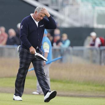 Darren Clarke walks down the 18th looking a little bemused at his display