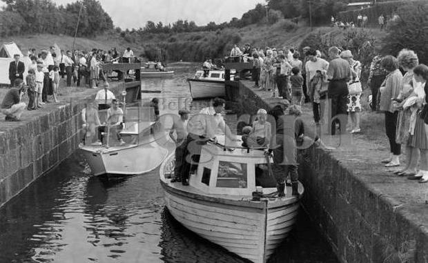 """""""Messing about in boats"""" is as much fun for the landlubbers who just sit and watch, as it is for the proud enthusiasts tending their craft in Portna Lock, on the Bann at Kilrea. 17/8/1964"""
