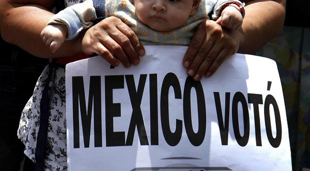 A woman carrying a baby shows a sign that reads 'Mexico voted, Pena Nieta didn't win' during a march in Mexico City (AP/Marco Ugarte)