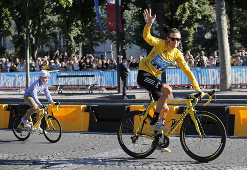 Bradley Wiggins, winner of the 2012 Tour de France cycling race rides up the Champs Elysees with his son during a parade after the last stage of the race in Paris, France, Sunday July 22, 2012. (AP Photo/Christophe Ena)