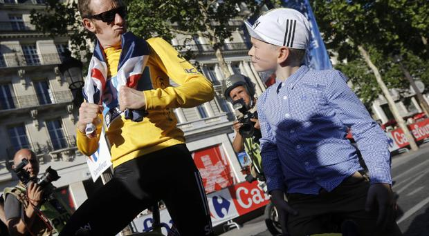 Bradley Wiggins, winner of the 2012 Tour de France cycling race, looks at his son Ben who has
