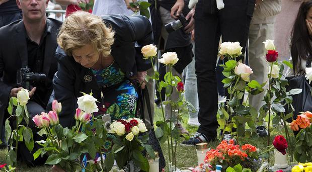 People lay down flowers outside the cathedral in Oslo on the first anniversary of the bombing and shooting rampage in Norway (AP)