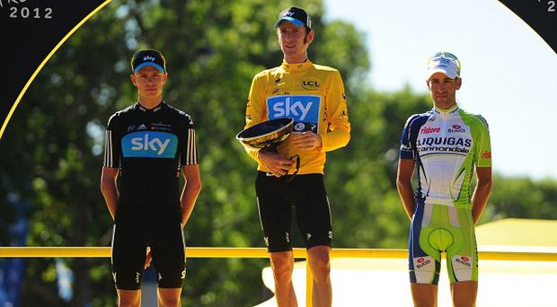Bradley Wiggins celebrates his Tour de France win with team mate Chris Froome, left, who came second, and third-placed rider Vincenzo Nibali