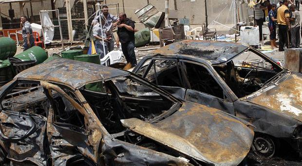 People inspect the aftermath of a car bomb attack in Baghdad's Shiite enclave of Sadr City, Iraq (AP)