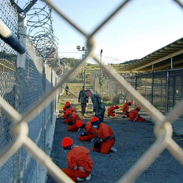 Detainees in orange jumpsuits at Camp X-Ray at Naval Base Guantanamo Bay, Cuba
