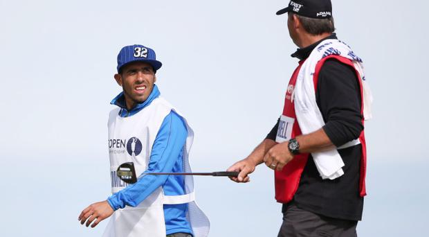 LYTHAM ST ANNES, ENGLAND - JULY 22: Footballer Carlos Tevez of Manchester City and Argentina working as a caddie for Andres Romero, chats with Judd Burkett during the final round of the 141st Open Championship at Royal Lytham & St. Annes Golf Club on July 22, 2012 in Lytham St Annes, England. (Photo by Ross Kinnaird/Getty Images)