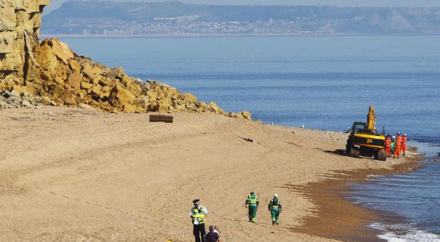 Rescuers work at the scene of a cliff landslide near Burton Bradstock, Dorset