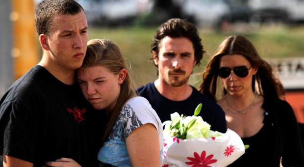 A couple embraces each other as actor Christian Bale holds flowers before placing them at the memorial across the street from the Century 16 movie theater