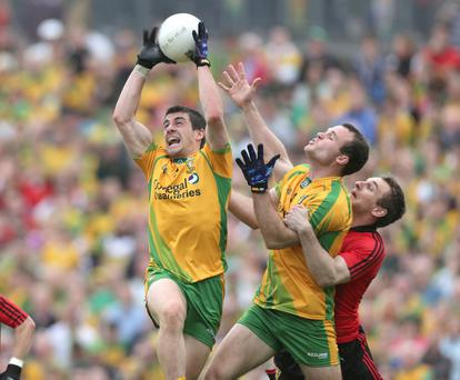There is no way through for Down's Eoin McCartan as his path to the ball is blocked by Donegal's Paddy McGrath and Neil McGee