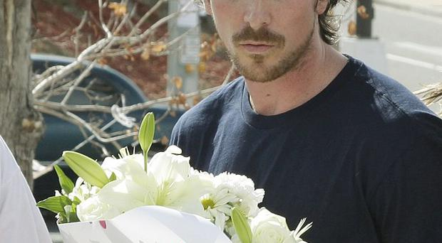 Actor Christian Bale carries flowers as he visits a memorial to the victims of Friday's mass shooting in Aurora, Colorado (AP)