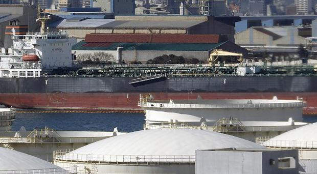 An oil tanker is moored near oil refineries in Kawasaki, west of Tokyo, as Japan reported its biggest half-year trade deficit (AP)