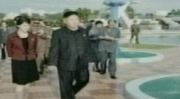 North Korean leder Kim Jong Un with a mystery woman who turns out to be his wife (AP)