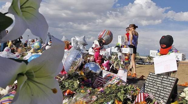 A woman holds flowers before placing them at a memorial across from the cinema in Aurora where 12 people were killed (AP)