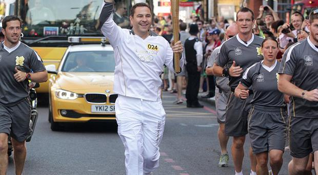David Walliams carries the Olympic Flame on the Torch Relay leg between Camden and Islington (Locog/PA)