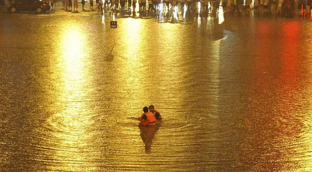 Rescuers search for victims near a flooded underpass after heavy rains in Beijing (AP Photo)