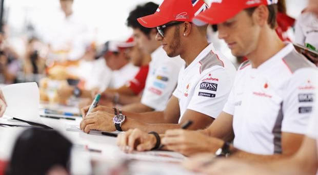 BUDAPEST, HUNGARY - JULY 26: Lewis Hamilton (C) of Great Britain and McLaren signs autographs for fans during previews to the Hungarian Formula One Grand Prix at the Hungaroring on July 26, 2012 in Budapest, Hungary. (Photo by Drew Gibson/Getty Images)