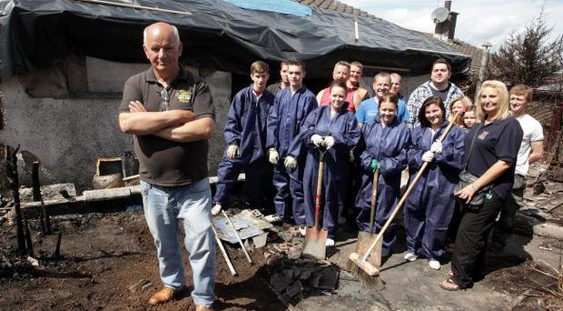 Brian McArthur with members of the Ballybeen community as they work to remove debris from his burnt-out house