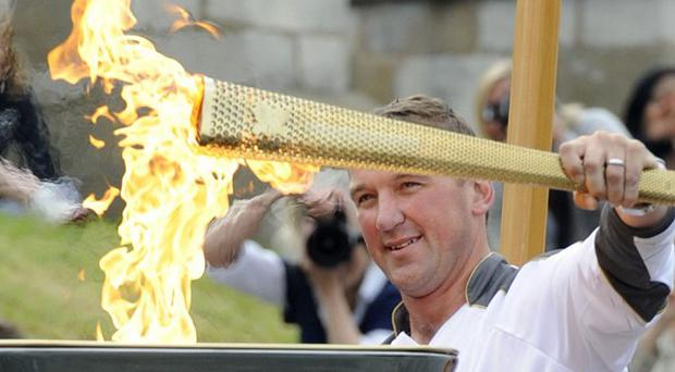 Olympic gold medallist rower Matthew Pinsent lighting the cauldron with the Olympic Flame on the royal row barge Gloriana