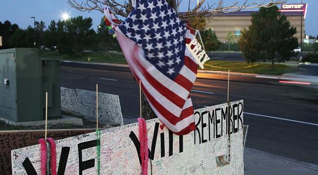 A sign that reads 'We Will Remember' hangs under a US flag across the street from the Century 16 cinema where 12 people were shot dead (AP)