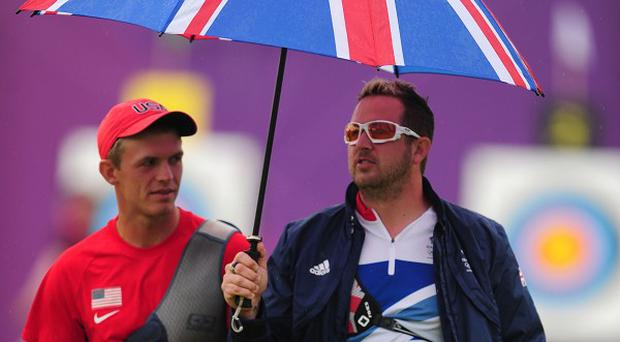 Great Britain's Larry Godfrey (right) and the USA's Jacob Wukie (left) share an umbrella during the Men's Individual Archery Ranking Round at Lords
