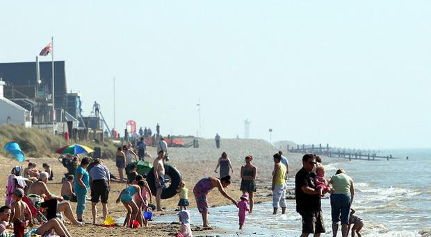A woman was pulled unconscious from the water after getting into difficulties at Camber Sands in East Sussex