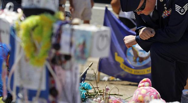 US air force staff sergeant Ryan Eanes kneels down at the memorial across from the Century 16 theatre in Aurora, Colorado (AP)