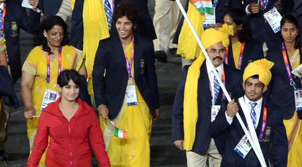 A member of the Olympics Opening Ceremony cast (front left) takes part in the athletes' parade alongside India's Olympic team