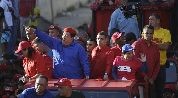 Hugo Chavez greets supporters as he arrives for a campaign rally in the Petare neighbourhood of Caracas (AP)