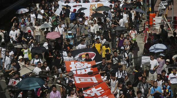 Thousands of people march on a downtown street in Hong Kong (AP)