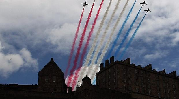 The Red Arrows perform a flypast over Edinburgh Castle to mark the opening ceremony of the Olympic Games