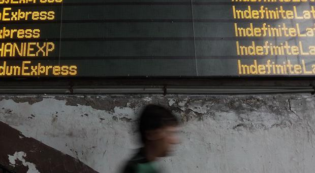 An Indian commuter walks past the status board for trains displaying Indefinite Late for all the trains following a power outage (AP)