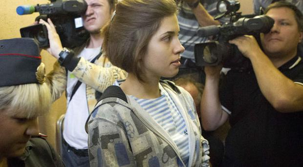 Nadezhda Tolokonnikova, center, a member of feminist punk group Pussy Riot is escorted to a court room in Moscow, Russia, Friday, July 20, 2012. The trial of feminist punk rockers who chanted a