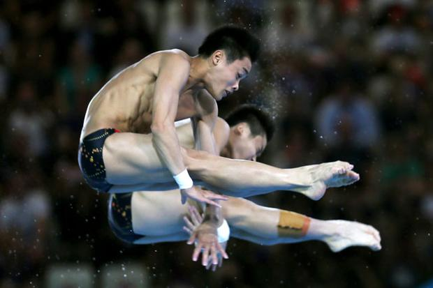 LONDON, ENGLAND - JULY 30: Yuan Cao and Yanquan Zhang of China compete in the Men's Synchronised 10m Platform Diving on Day 3 of the London 2012 Olympic Games at the Aquatics Centre on July 30, 2012 in London, England. (Photo by Clive Rose/Getty Images)