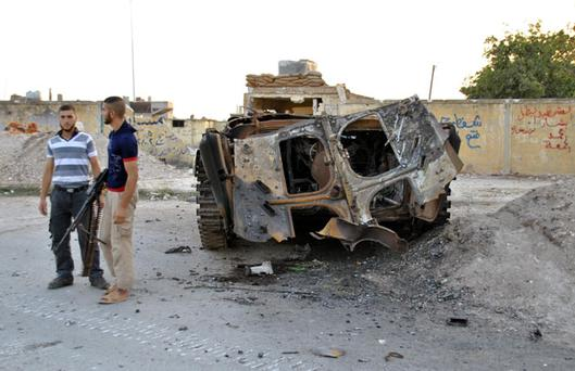 In this Friday, July 27, 2012 photo, armed Syrian rebels stand beside a destroyed Syrian army armored vehicle in Homs, Syria. It has been a difficult two weeks for the Syrian government with rebel assaults first on the capital, Damascus, and then on Aleppo, as well as several high-profile defections and a bomb that killed four top security officials. (AP Photo/Fadi Zaidan)