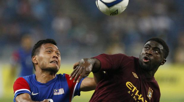 Manchester City's Kolo Toure, right, and Malaysia's Mohd Safee Mohd Sali battle for the ball during their friendly soccer match in Kuala Lumpur, Malaysia, Monday, July 30, 2012. (AP Photo/Lai Seng Sin)