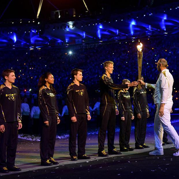 Sir Steve Redgrave hands the torch to young torch bearers Callum Airlie, Jordan Duckitt, Desiree Henry, Katie Kirk, Cameron MacRitchie, Aidan Reynolds and Adelle Tracey
