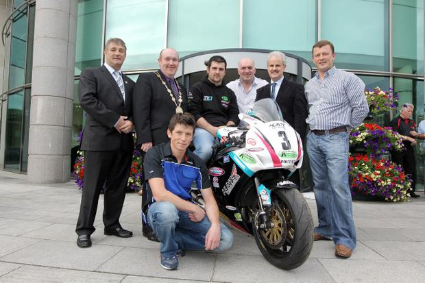Michael Dunlop puts the wheels in motion at the launch of the Ulster Grand Prix alongside Eddie Rowan (NITB), William Leathem (Mayor of Lisburn), Dan Kneen (rider), Noel Johnston (Clark of the Course), Cllr Thomas Beckett (Chairman of Lisburn City Council's Leisure Services Committee) and Mark McKinstry (McKinstry Skip Hire)