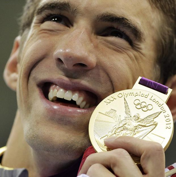 Michael Phelps poses with his gold medal for the men's 4x200-metre freestyle relay swimming final (AP/Matt Slocum)